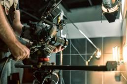 A man adjusting a TV video camera in a studio environment