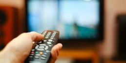 Person pressing a button on a TV remote pointed at a blurred out TV in the background